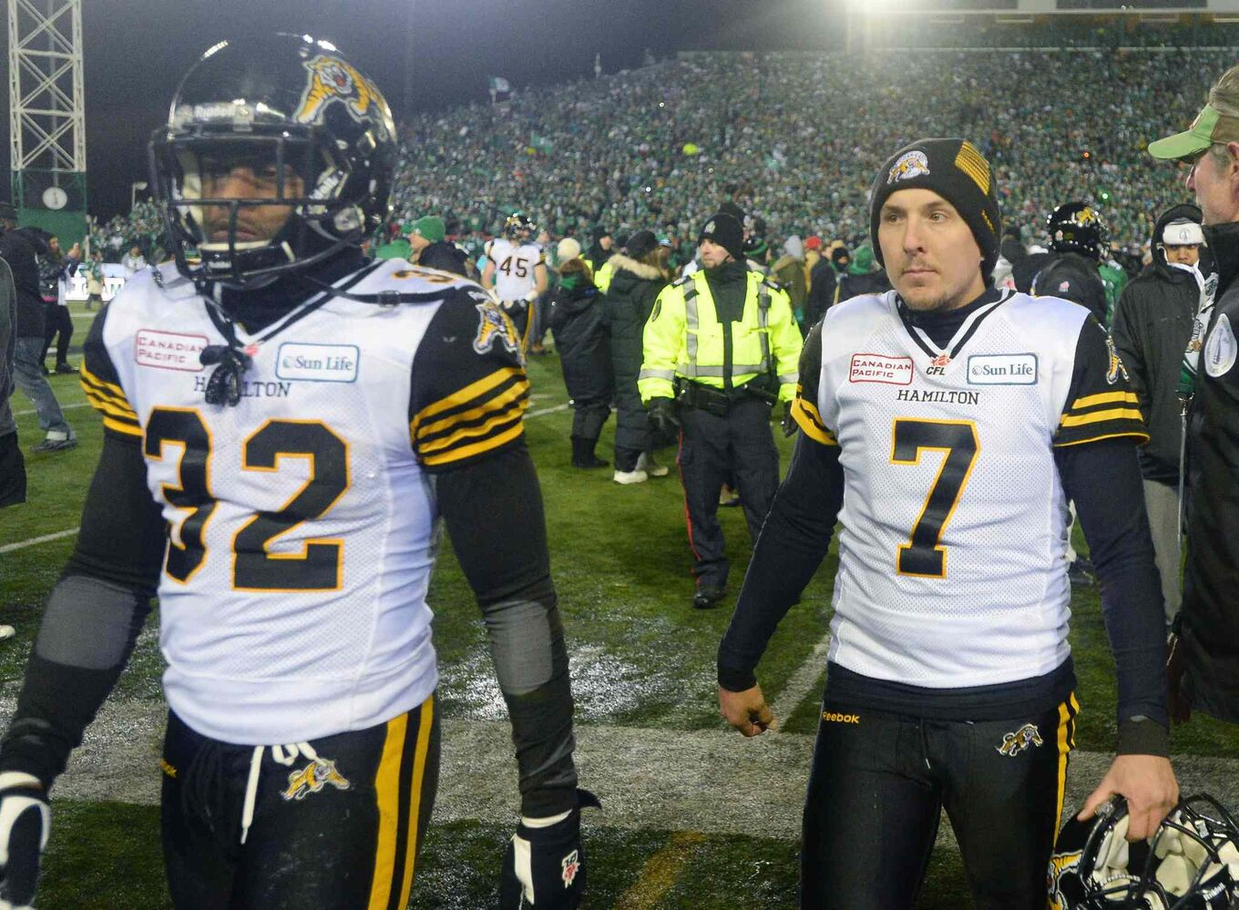 Hamilton Tiger-Cats running back C.J. Gable (left) and kicker Luca Congi walk off the field after losing to the Saskatchewan Roughriders. (Liam Richards / The Canadian Press)