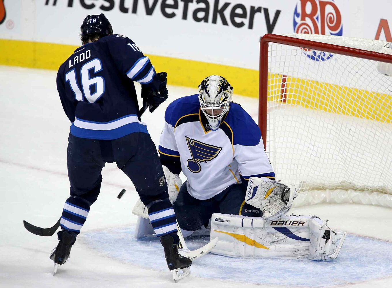 Winnipeg Jets captain Andrew Ladd tries to screen St. Louis Blues goaltender Brian Elliot during the first period.