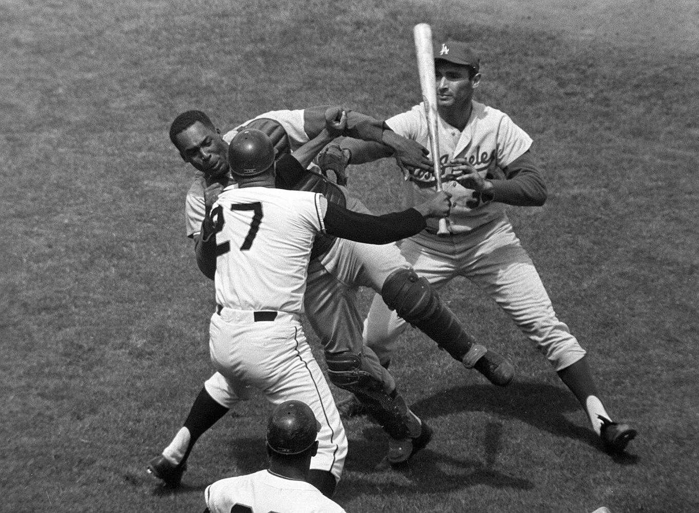 In this Aug. 22, 1965, file photo from Candlestick Park, San Francisco Giants pitcher Juan Marichal (27) swings a bat at Los Angeles Dodgers catcher John Roseboro (top left) as Dodgers pitcher Sandy Koufax (rear right) tries to break it up.