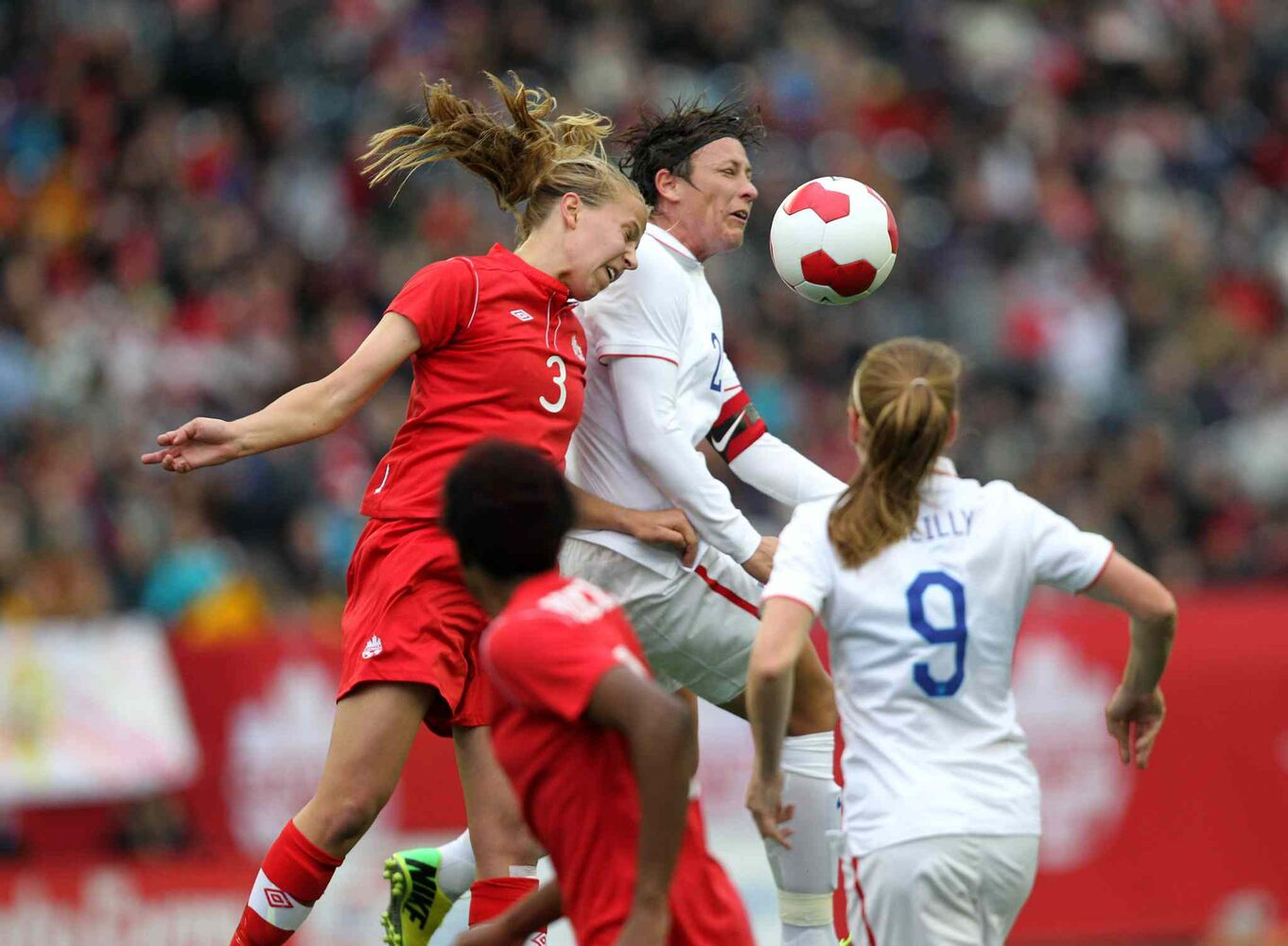 Canada's Rebecca Quinn (#3) and USA Abby Wambach, (#20) headbutt the ball during the first half  of the Canada vs USA women's international soccer match Thursday. (Ruth Bonneville / Winnipeg Free Press)