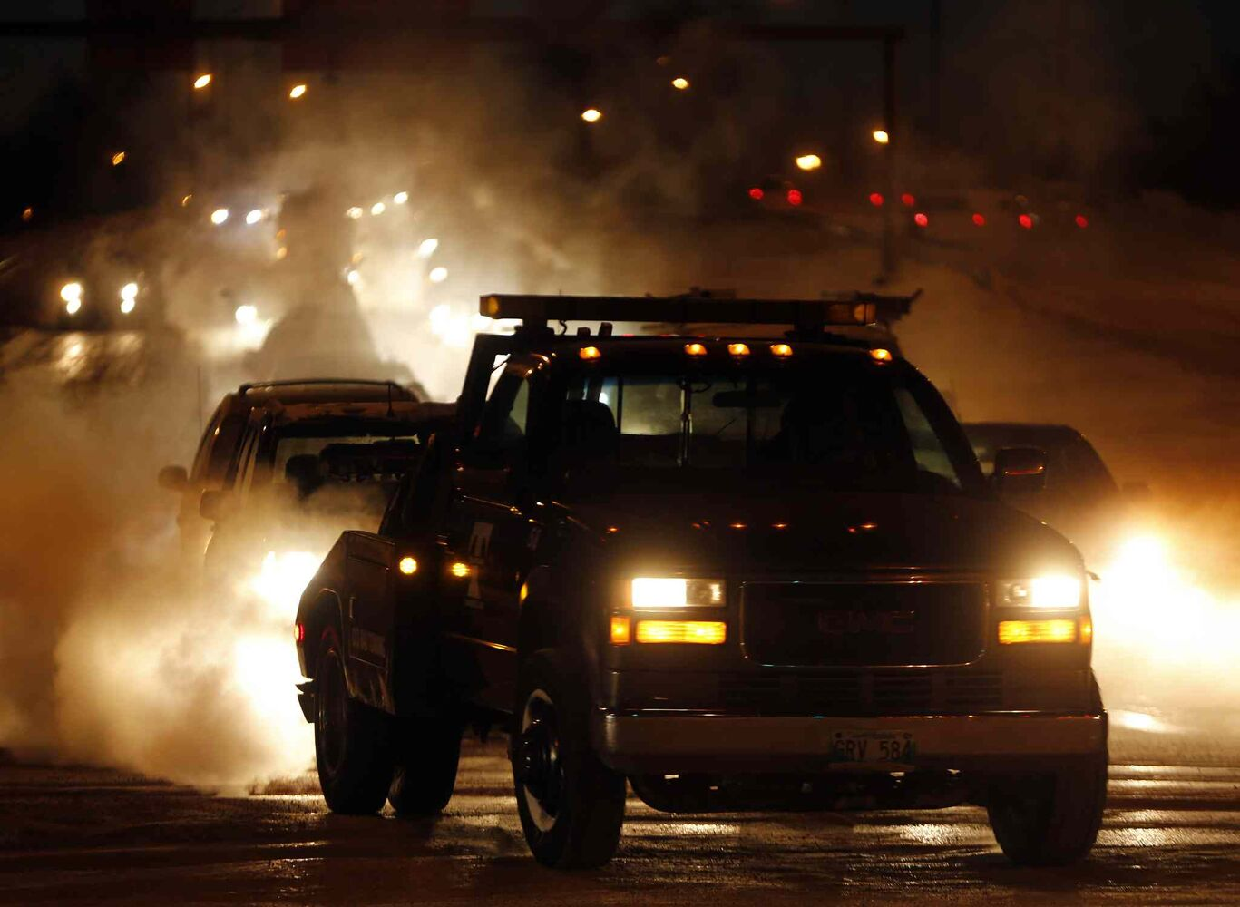Tow trucks are in high demand and are out early to help as exhaust fog causes visibility problems for drivers on Chief Peguis Trail at Main St. Tuesday in Winnipeg. (KEN GIGLIOTTI / WINNIPEG FREE PRESS)