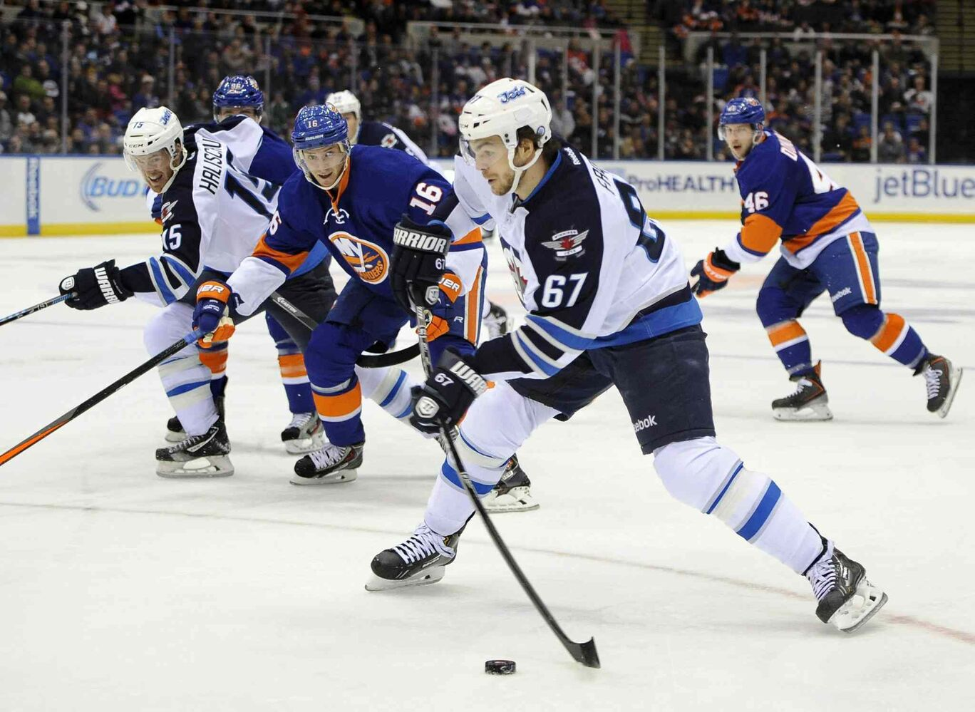 Winnipeg Jets forward Michael Frolik (67) takes a shot on goal as Peter Regin (16) of the New York Islanders in the first period. (Kathy Kmonicek / The Associated Press)