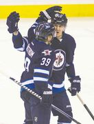 The Jets' Tobias Enstrom (39)  celebrates his goal with a Mark Scheifele during the first period Friday.