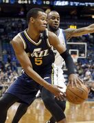 Utah Jazz's Rodney Hood, left, makes a backhand pass as Minnesota Timberwolves' Lorenzo Brown defends in the first quarter of an NBA basketball game, Monday, March 30, 2015, in Minneapolis. (AP Photo/Jim Mone)