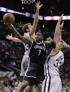 Brooklyn Nets' Joe Johnson (7) drives between San Antonio Spurs' Marco Belinelli (3) and Boris Diaw (33) during the first half of an NBA basketball game, Saturday, Nov. 22, 2014, in San Antonio, Texas. (AP Photo/Eric Gay)