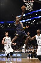 Cleveland Cavaliers forward LeBron James (23) drives the ball to the basket between Brooklyn Nets center Brook Lopez (11) and guard Markel Brown (22) in the first half of an NBA basketball game on Friday, March 27, 2015, in New York. (AP Photo/Kathy Kmonicek)