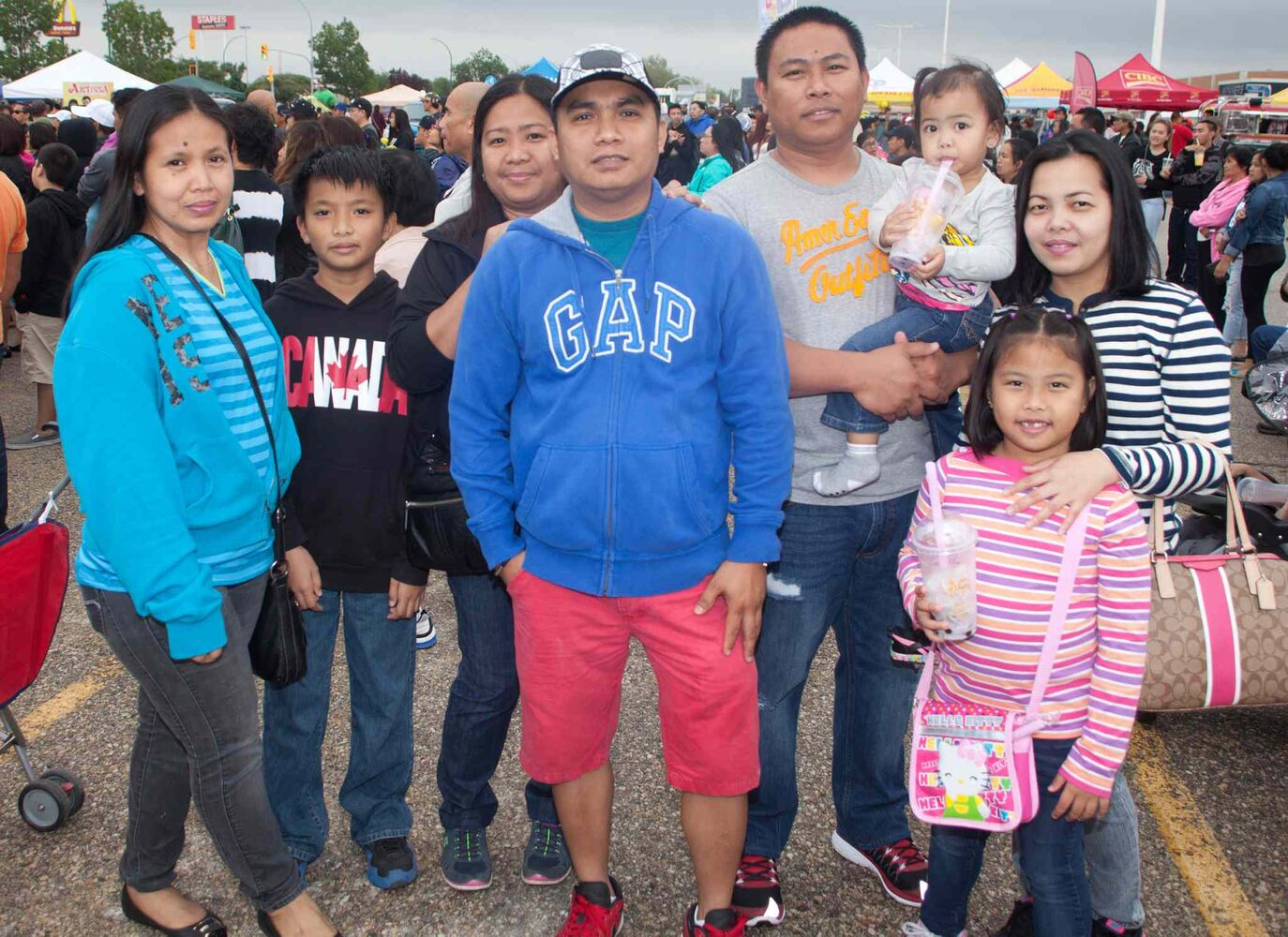 The Manitoba Filipino Street Festival didn't let the rain dampen its annual parade and party at Garden City Shopping Centre on Aug. 22, 2015. Pictured, from left, are Cherilyn Bautista, Aldiun Bautista, Marijane Banta, Roneil Banta, Melvin Magnayi, Ednalene Magnayi, Audrey Magnayi and Ashley Magnayi. (JOHN JOHNSTON FOR THE WINNIPEG FREE PRESS)