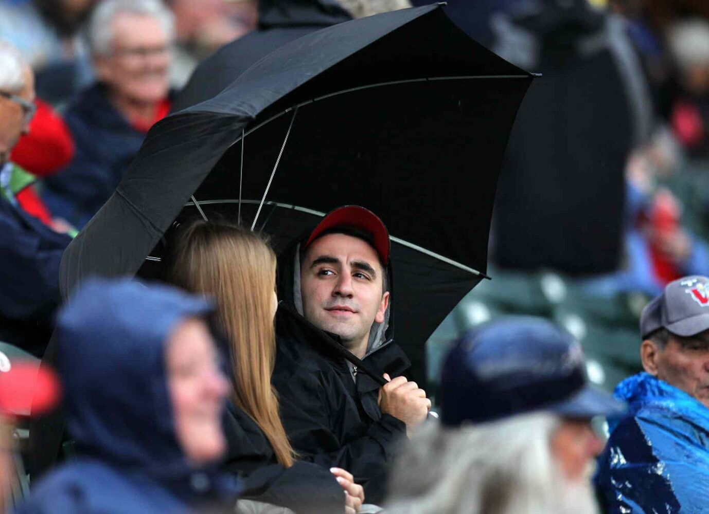 A few fans sheltered under umbrellas at Shaw Park Wednesday evening but short showers didn't dampen the enthusiasm as the Goldeyes and Saltdogs opened up the playoff season. (Phil Hossack / Winnipeg Free Press)