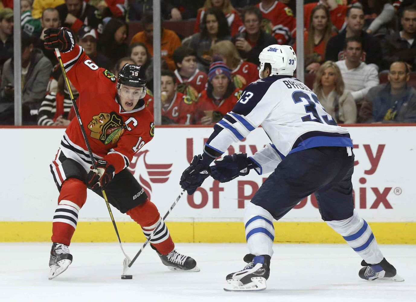 Blackhawks captain Jonathan Toews tries to dangle past the Jets' Dustin Byfuglien. (Charles Rex Arbogast / The Associated Press)