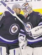 Michael Hutchinson (right) celebrates his first NHL win with Ondrej Pavelec, a shootout win over the Boston Bruins in April.
