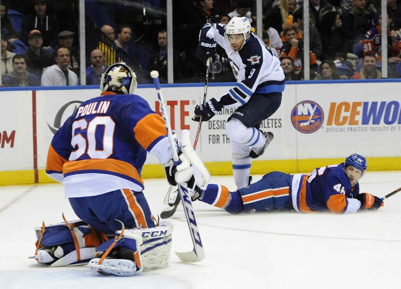 Winnipeg Jets' Evander Kane (centre) skips over a fallen New York Islanders' Matt Donovan (right) to take a shot on goal at goalie Kevin Poulin in the first period. (Kathy Kmonicek / The Associated Press)