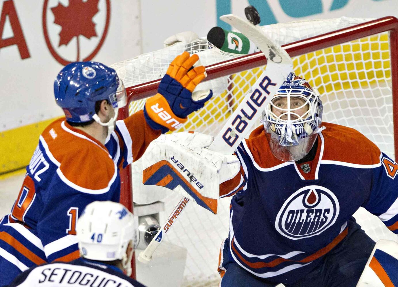 Winnipeg Jets' Devin Setoguchi (40) and Edmonton Oilers' Justin Schultz (19) look for the rebound as Oilers goalie Devan Dubnyk (40) makes a save during second-period NHL hockey action in Edmonton.