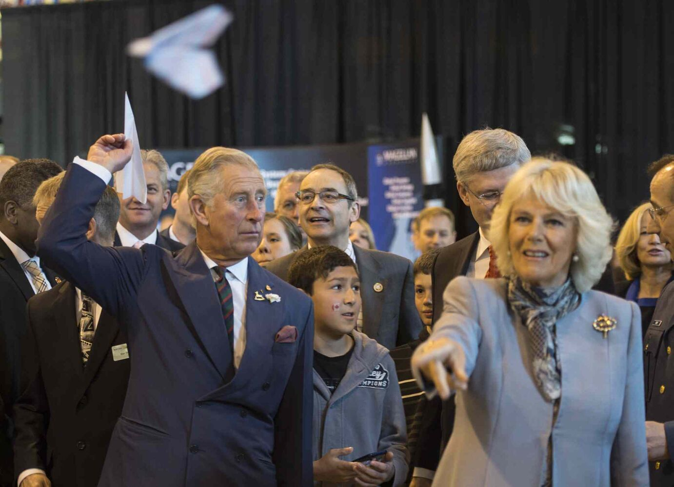 Prince Charles, left, and his wife Camilla throw paper airplanes with Prime Minister Stephen Harper (obscured) at the Stevenson Hangar.  (Paul Chiasson / The Canadian Press)