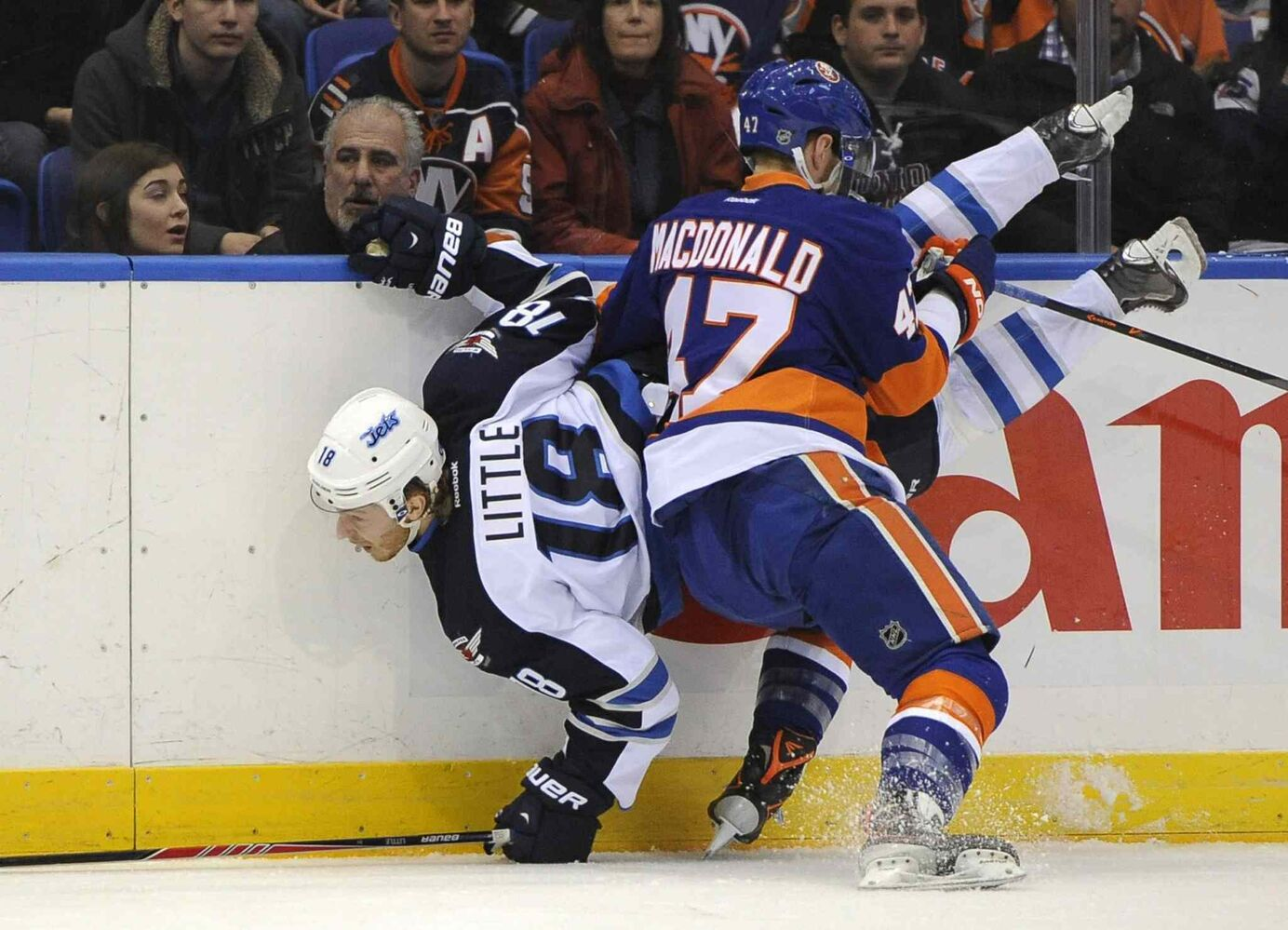 Andrew MacDonald (right) of the New York Islanders shoves Winnipeg Jets forward Bryan Little into the boards in the first period of Wednesday's night's game in Uniondale, N.Y. (Kathy Kmonicek / The Associated Press)
