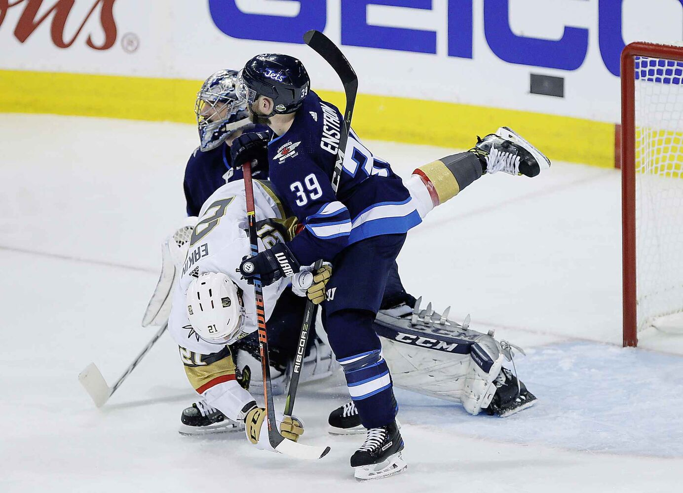 JOHN WOODS / THE CANADIAN PRESS</p><pWinnipeg Jets' Toby Enstrom (39) takes Vegas Golden Knights' Cody Eakin (21) out of the play in front of goaltender Connor Hellebuyck (37) during third period of game one action in the NHL Western Conference Final in Winnipeg on Saturday, May 12, 2018.</p>