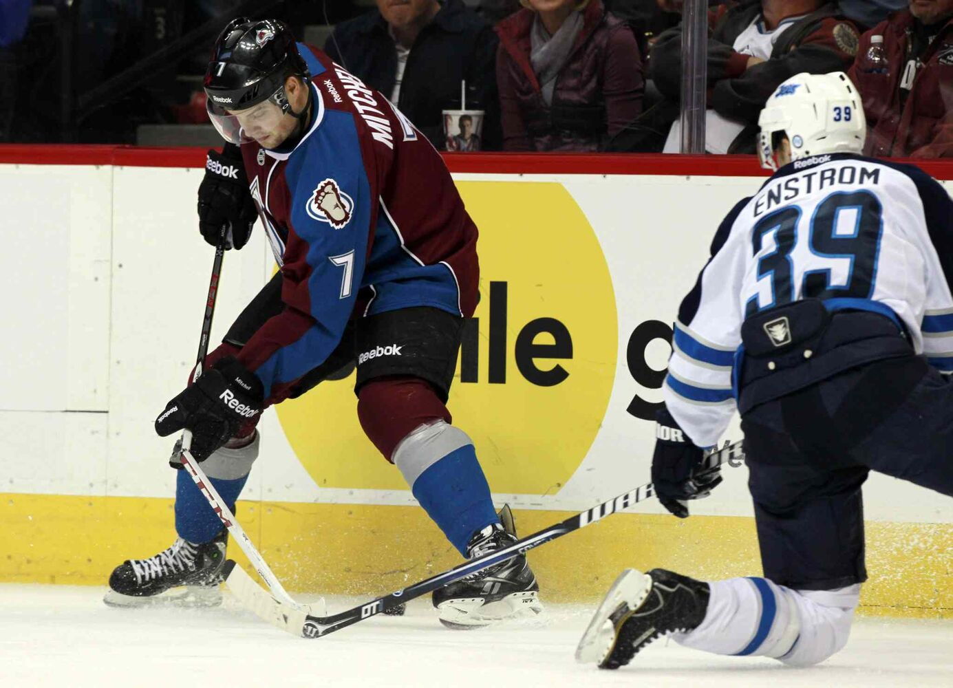 Colorado Avalanche center John Mitchell (left) has his stick break while trying to clear the puck along the boards as he battles with Tobias Enstrom in the second period. (David Zalubowski / The Associated Press)