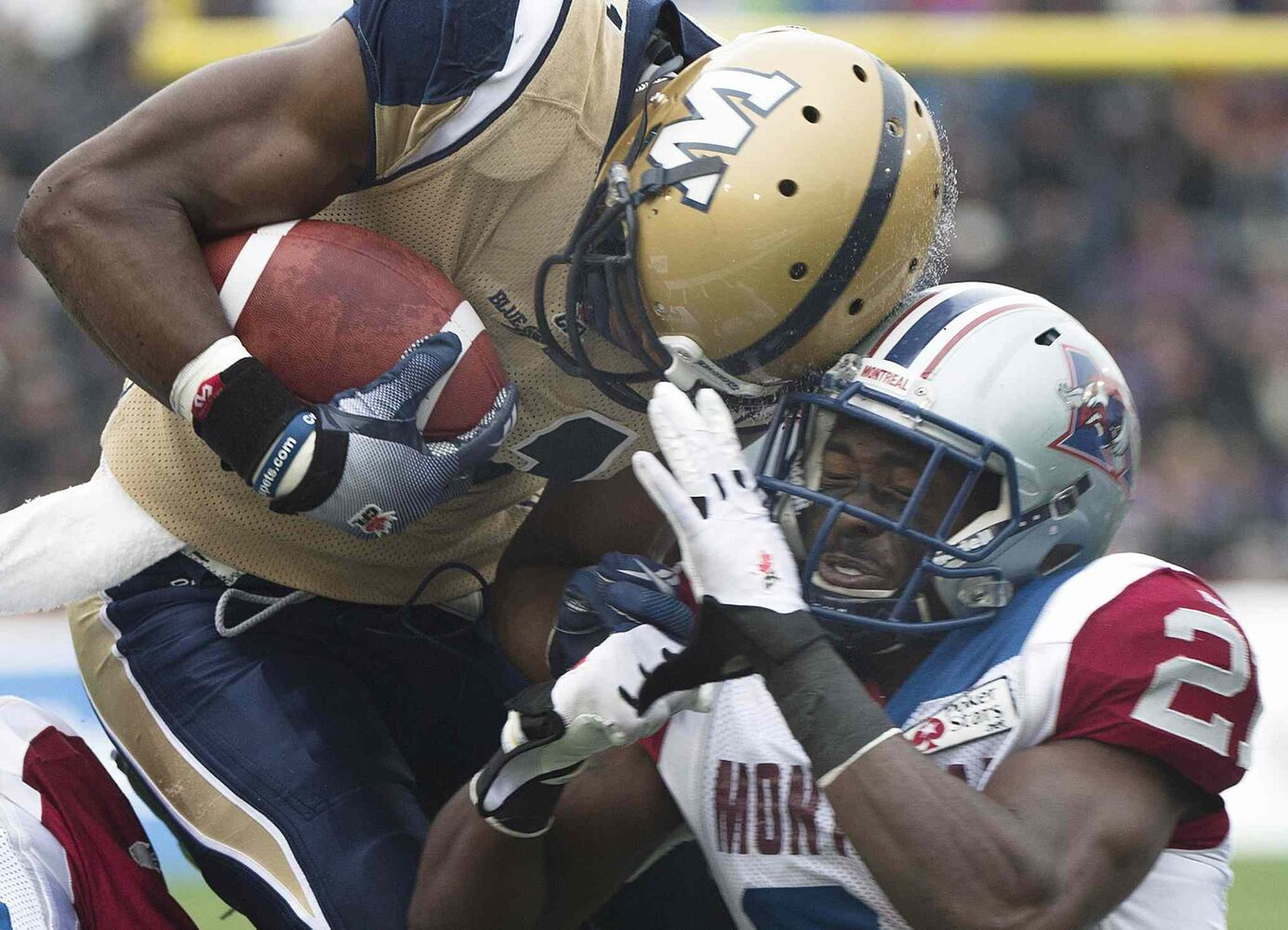Winnipeg Blue Bombers' Cory Watson, left, is tackled by Montreal Alouettes' Mike Edem during first half CFL football action in Montreal, Monday. Winnipeg won, 34-27. (Graham Hughes / The Canadian Press)