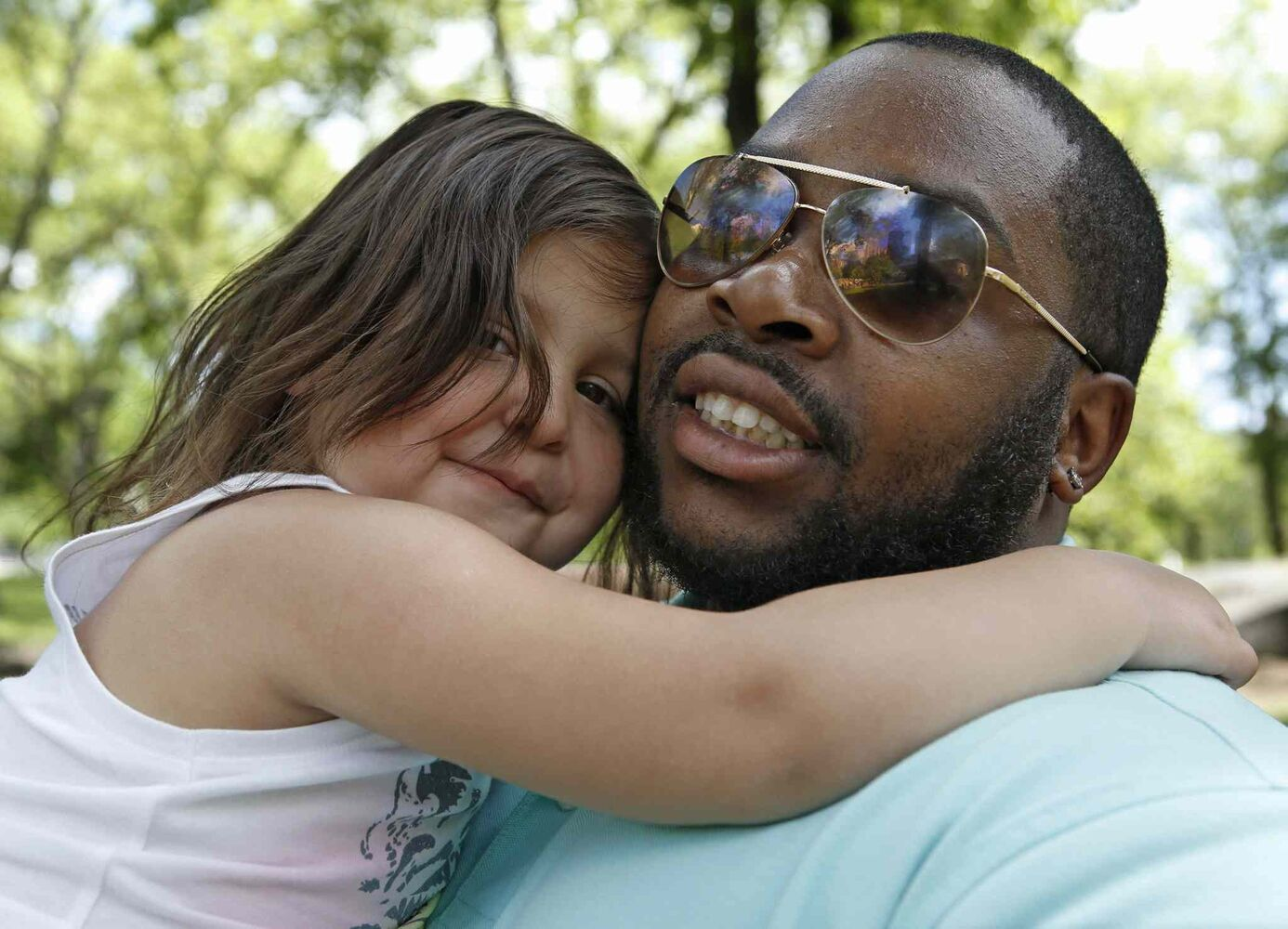 "Troy Johnson, 30, of Philadelphia, holds his daughter, Isabella, 4, after visiting the American Museum of Natural History with his son Wayne, 7 in New York. ""It's about putting them before yourself,"" said Johnson. ""We don't really do anything outside of our family element. I worked all night, I work in a hospital, but they've never been to New York, so we just got up and came in.""  (Kathy Willens / The Associated Press)"