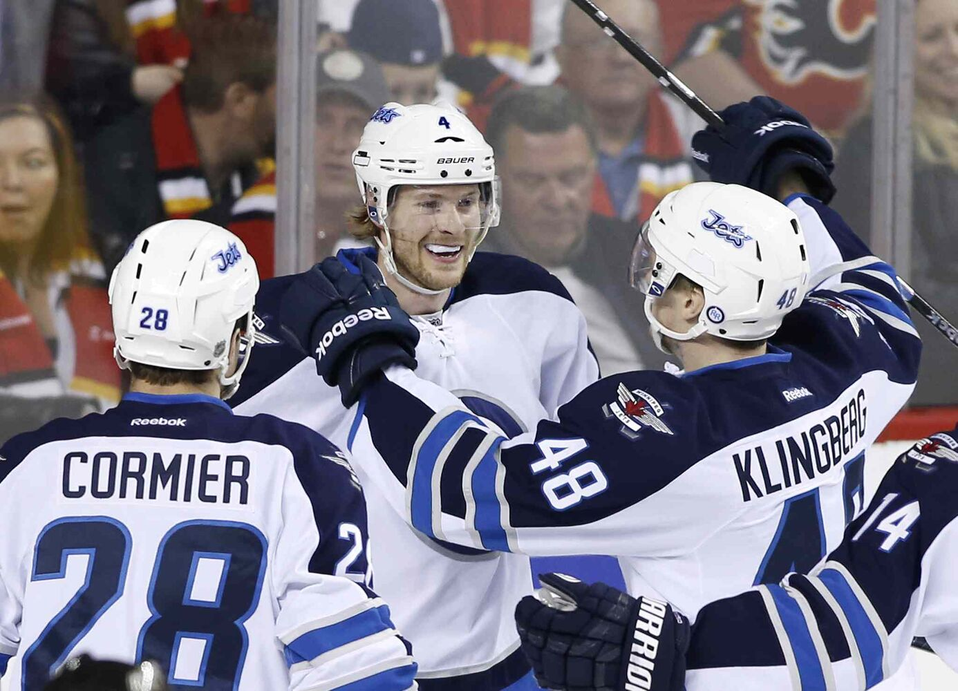Winnipeg Jets' Paul Postma, centre, celebrates his game-winning goal against the Calgary Flames with Patrice Cormier, left, and Carl Klingberg on Friday to end the Jets' final game of the season.