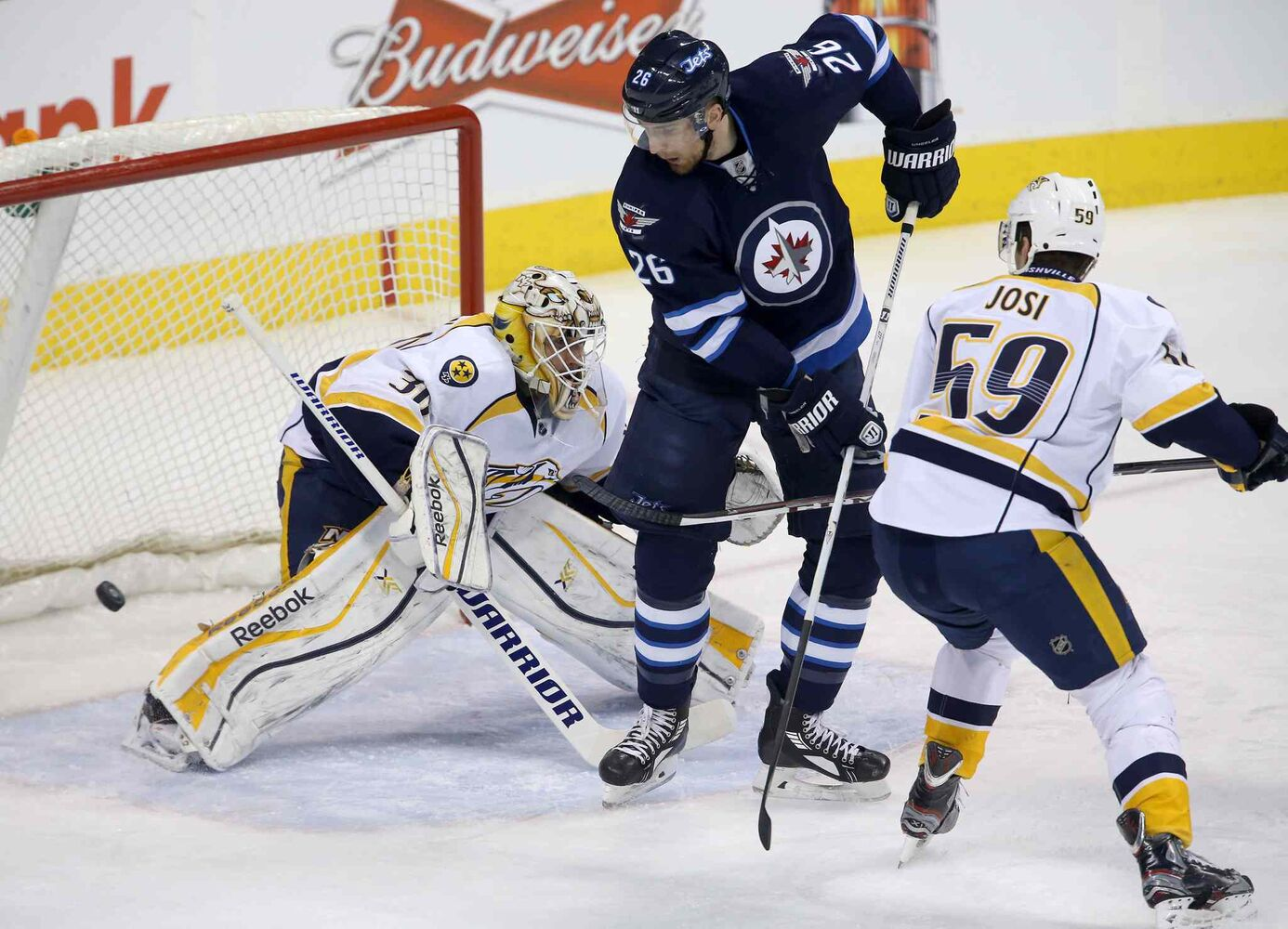 A shot by Winnipeg Jets' Chris Thorburn (22), not shown, beats Nashville Predators' goaltender Carter Hutton (30) as Jets' Blake Wheeler (26) and Predators' Roman Josi (59) battle in front of the net during first period at Winnipeg's MTS Centre Tuesday. (Trevor Hagan / The Canadian Press)