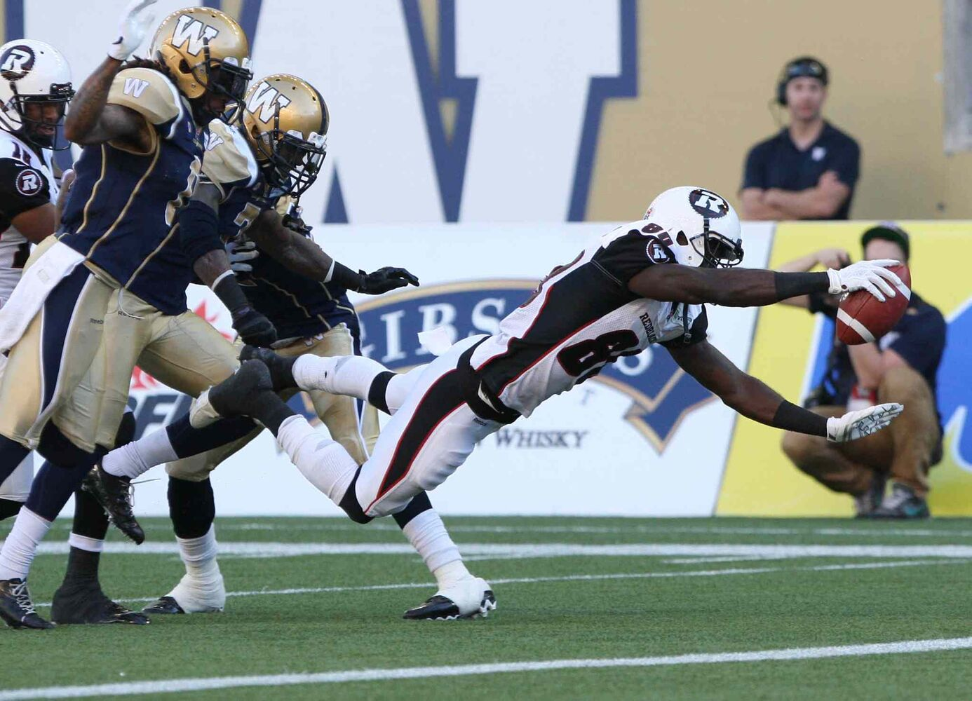 Winnipeg Blue Bombers could only watch as Ottawa Redblacks' Dobson Collins dives in for a first-quarter touchdown during CFL action at Investors Group Field in Winnipeg Thursday night. (JOE BRYKSA / WINNIPEG FREE PRESS)