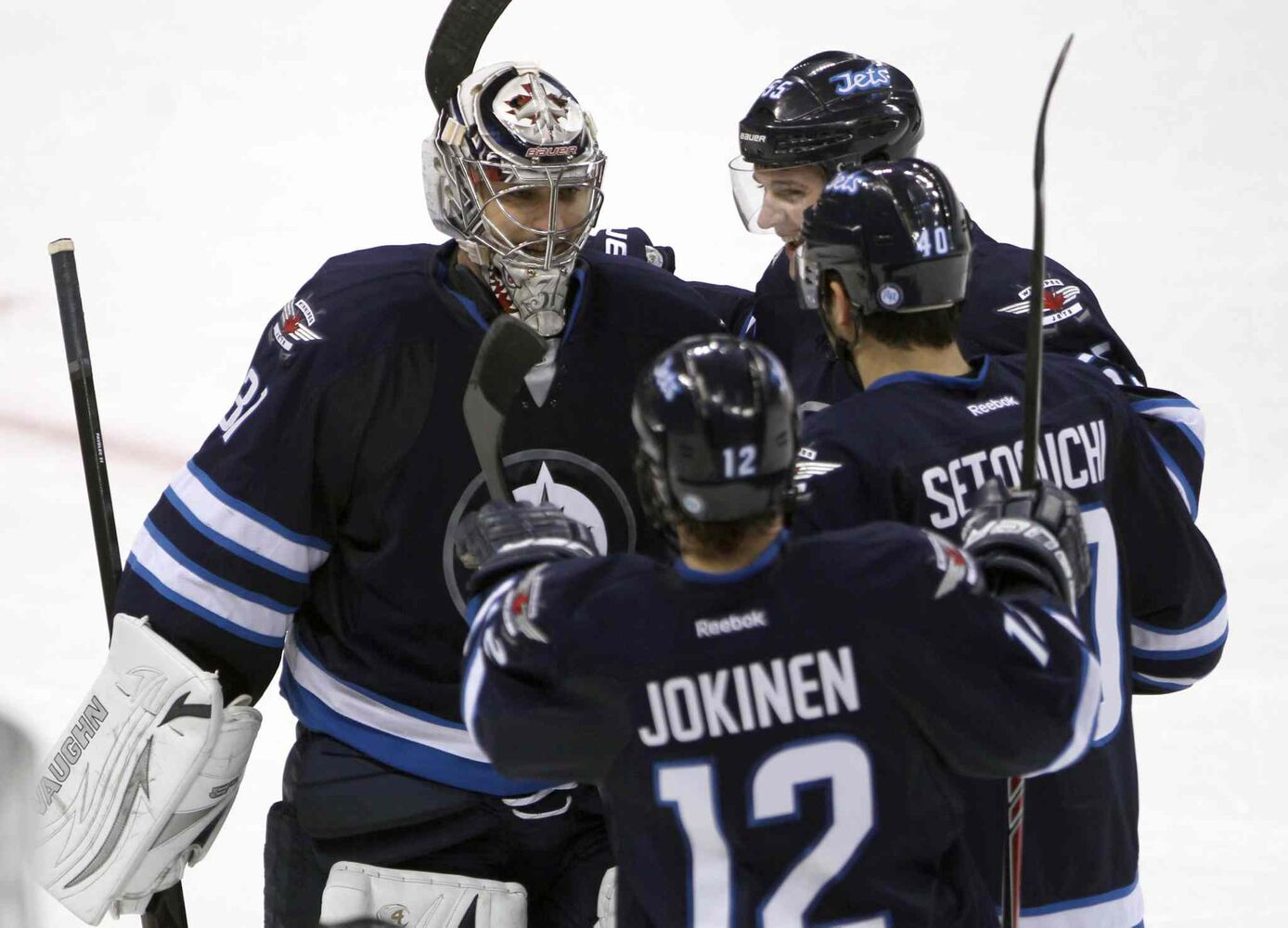 Winnipeg Jets goaltender Ondrej Pavelec celebrates the shootout win with teammates (from top) Mark Scheifele, Devin Setoguchi and Olli Jokinen. (JOE BRYKSA / WINNIPEG FREE PRESS)