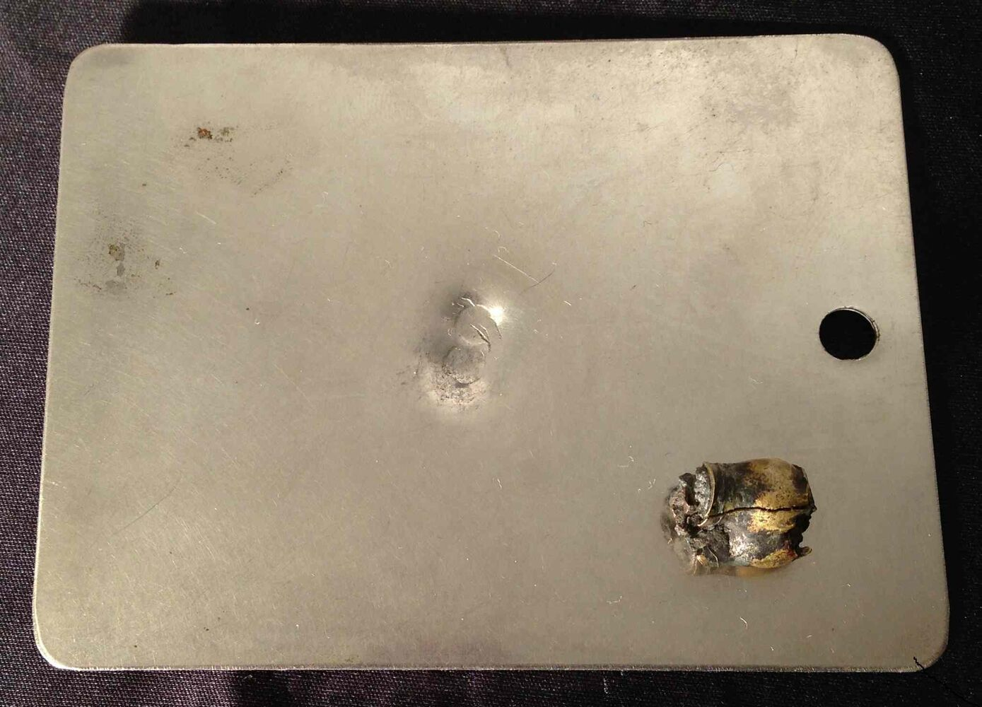 A dented shaving mirror which saved John Falloon's life during the First World War. The mirror — and a deck of cards over it — stopped a bullet. The bullet fragment is on the mirror. (Submitted photo)