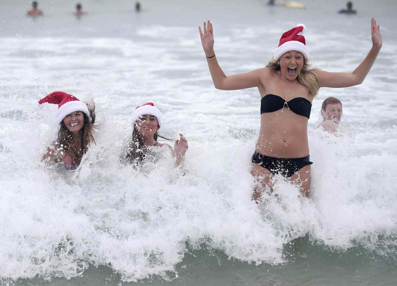 What better way to mark Christmas than take a dip in the ocean, in Australia? Lucy O'Grady, Tanya O'Grady and Lid O'Grady, all from Birmingham in the United Kingdom, splash around at Bondi Beach as they celebrate Christmas Day in Sydney. (The Associated Press)