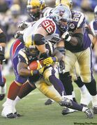 Blue Bombers running back Chris Garrett is brought down by Montreal Alouettes tackle J.P. Bekasiak (96) during first-half action.