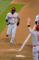 Cincinnati Reds' Brandon Phillips scores during the ninth inning of a baseball game against the St. Louis Cardinals on Wednesday, Aug. 20, 2014, in St. Louis. The Cardinals won 7-3. (AP Photo/Scott Kane)