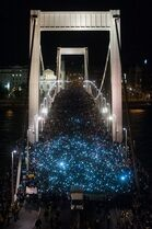 Thousands of demonstrators flash their mobile phones as they march through Elizabeth Bridge across River Danube as they protest against an internet tax planned to be introduced by the Hungarian government for the second time in two days in front of the Ministry of National Economy in Budapest, Hungary, Tuesday, Oct. 28, 2014. Tens of thousands of protesters marched Tuesday against a plan by the Hungarian government to tax Internet use from 2015. (AP Photo/MTI, Janos Marjai)