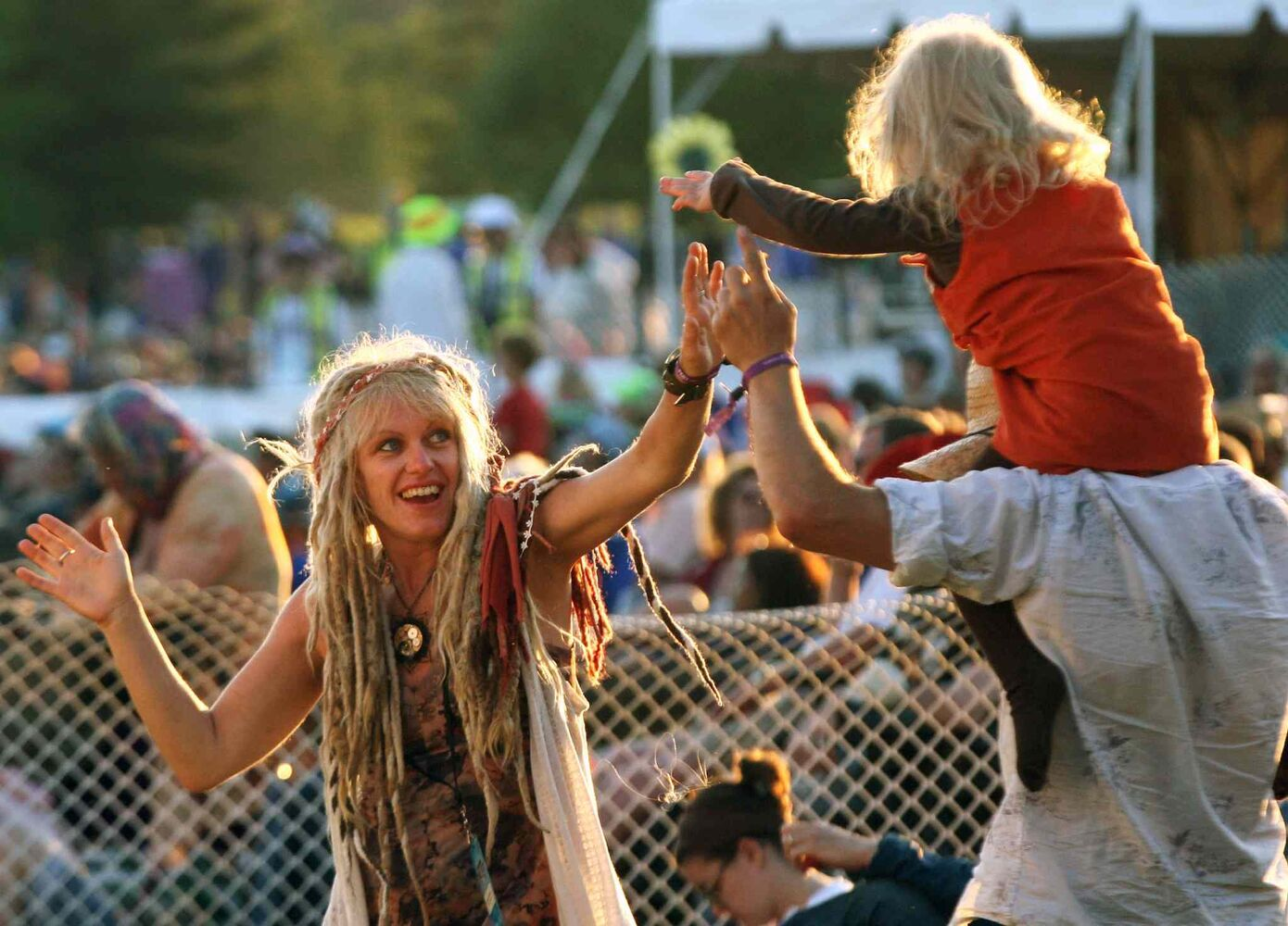 Briar MacDonald goes for a ride on friend Marc Simard's shoulders as mom Devaki MacDonald looks on at the  Winnipeg Folk Festival Friday night. (Joe Bryksa / Winnipeg Free Press)