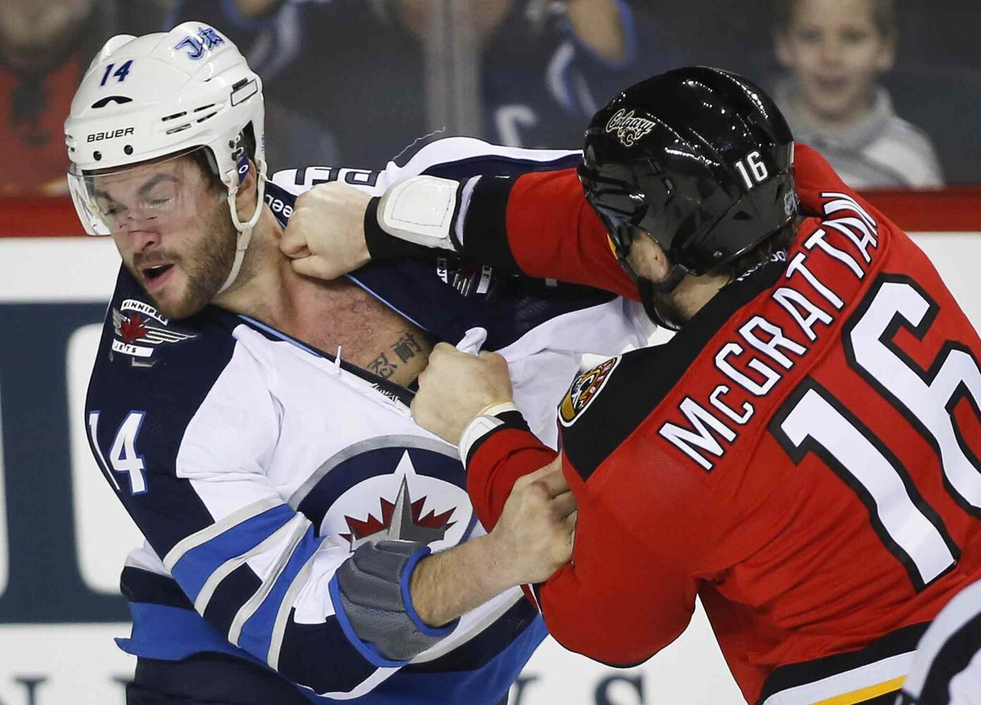 Winnipeg Jets' Anthony Peluso, left, fights Calgary Flames' Brian Mcgrattan during first period NHL hockey action in Calgary, Thursday. (Jeff McIntosh / The Canadian Press)