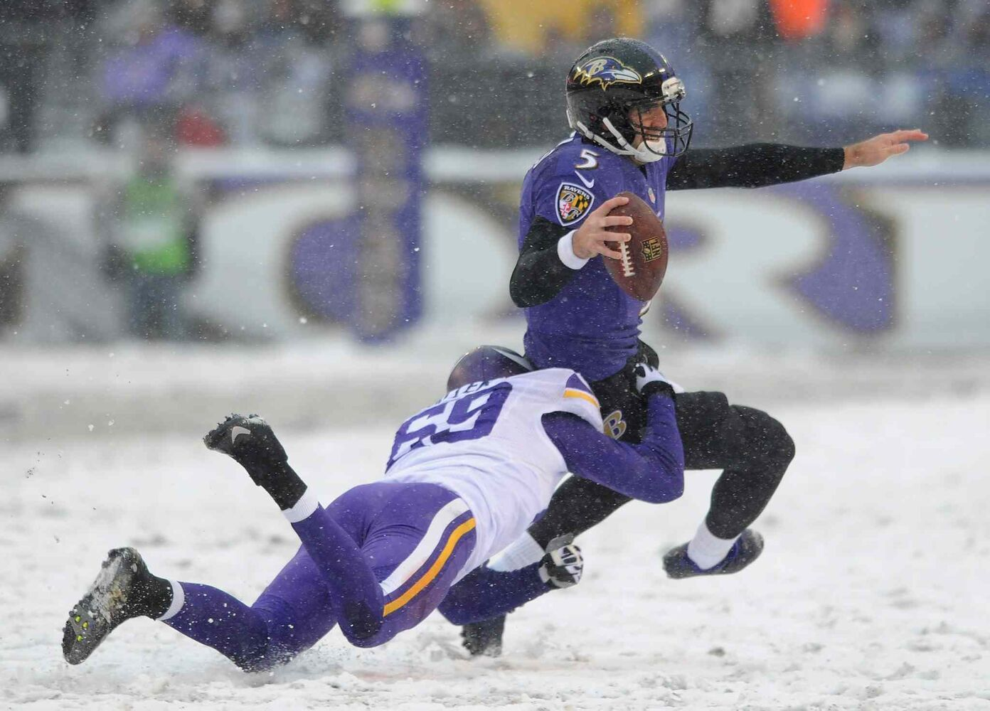 Baltimore Ravens quarterback Joe Flacco (right) is tackled by Minnesota Vikings defensive end Jared Allen as he rushes the ball in the first half.