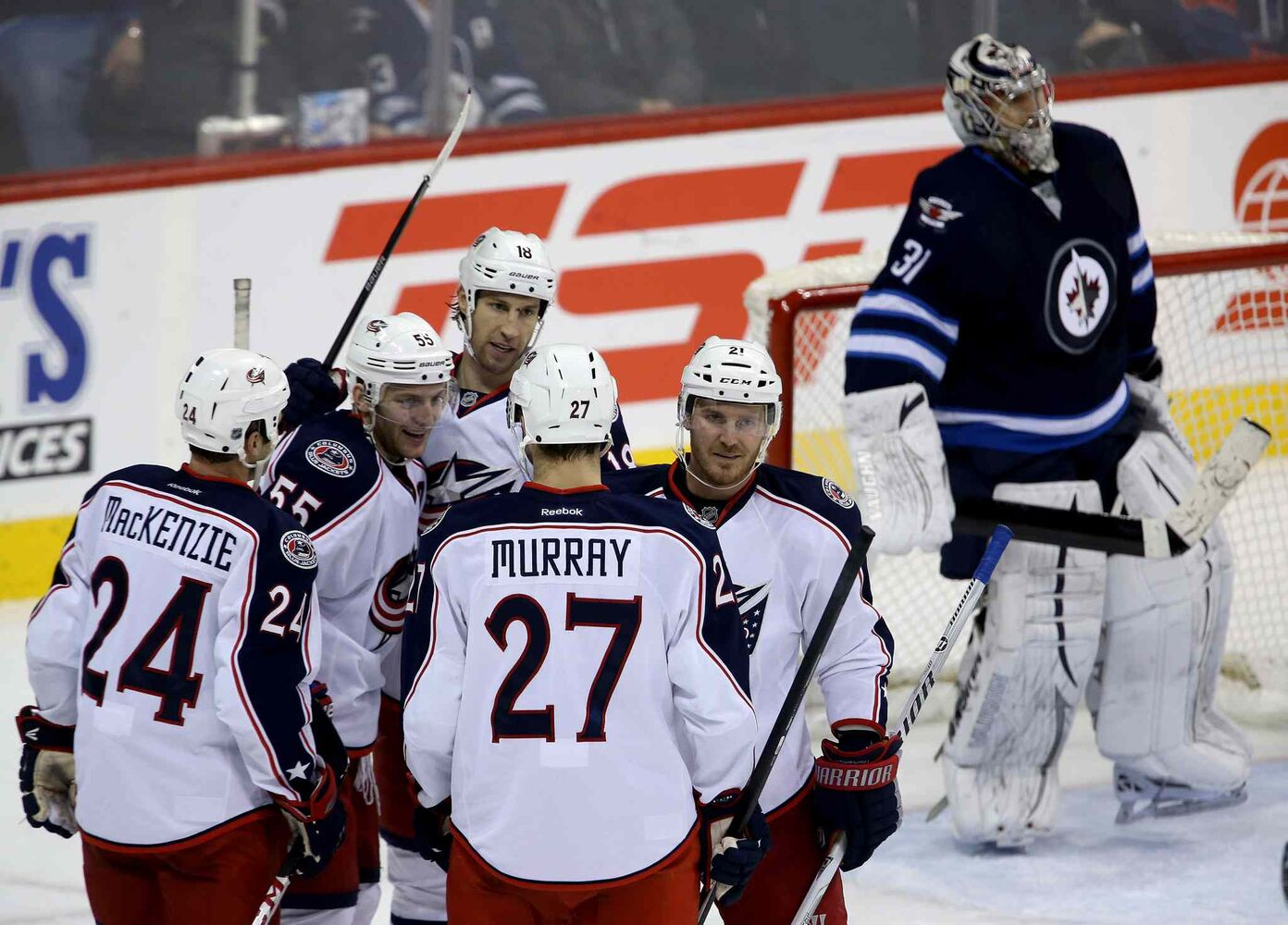 Columbus Blue Jackets' Derek MacKenzie (24), Mark Letestu (55), RJ Umberger (18), Ryan Murray (27) and James Wisniewski (21) celebrate after Letestu scored on Winnipeg Jets' goaltender Ondrej Pavelec (31) during the third period Saturday. (Trevor Hagan / Winnipeg Free Press)