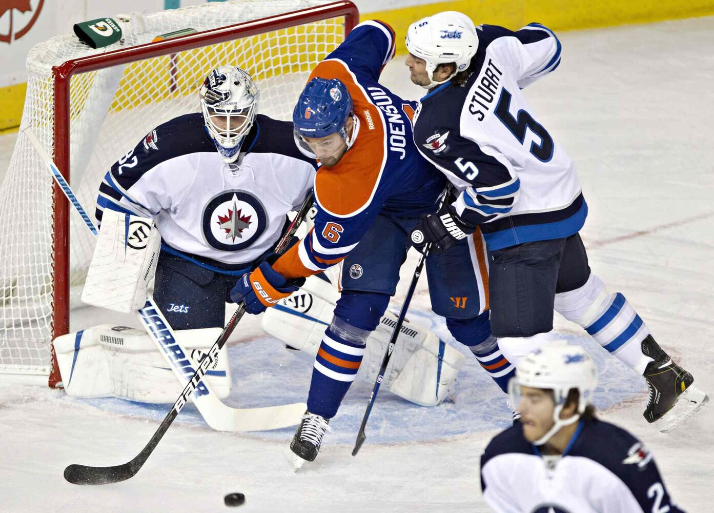 Winnipeg Jets goaltender Edward Pasquale makes a save as Mark Stuart (5) and Edmonton Oilers Jesse Joensuu (6) battle for the rebound during the first period. (Jason Franson / The Canadian Press)