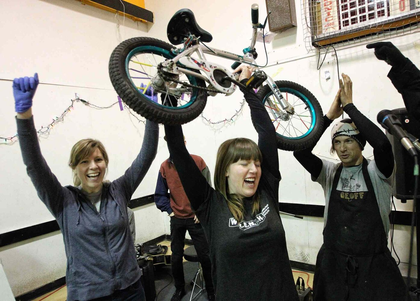 Robin Ellis (centre), a volunteer co-ordinator, cheers with other volunteers as she holds up the 200th bike to be repaired during the marathon.. (MIKE DEAL / WINNIPEG FREE PRESS)