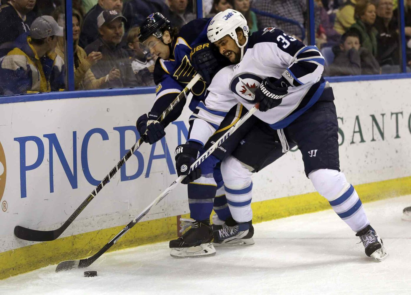Winnipeg Jets forward Dustin Byfuglien and the St. Louis Blues Kevin Shattenkirk chase after a loose puck during the first period. (JEFF ROBERSON / THE ASSOCIATED PRESS)