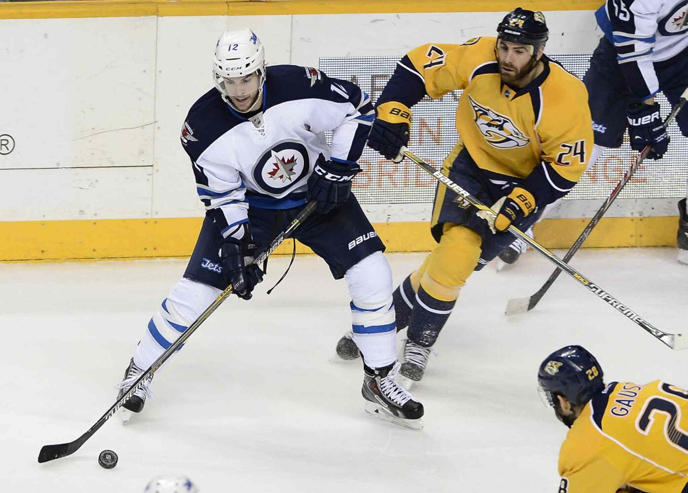 Winnipeg Jets right wing Drew Stafford, left, passes the puck as Nashville Predators left wing Eric Nystrom (24) defends in the second period. (Mark Zaleski / The Associated Press)