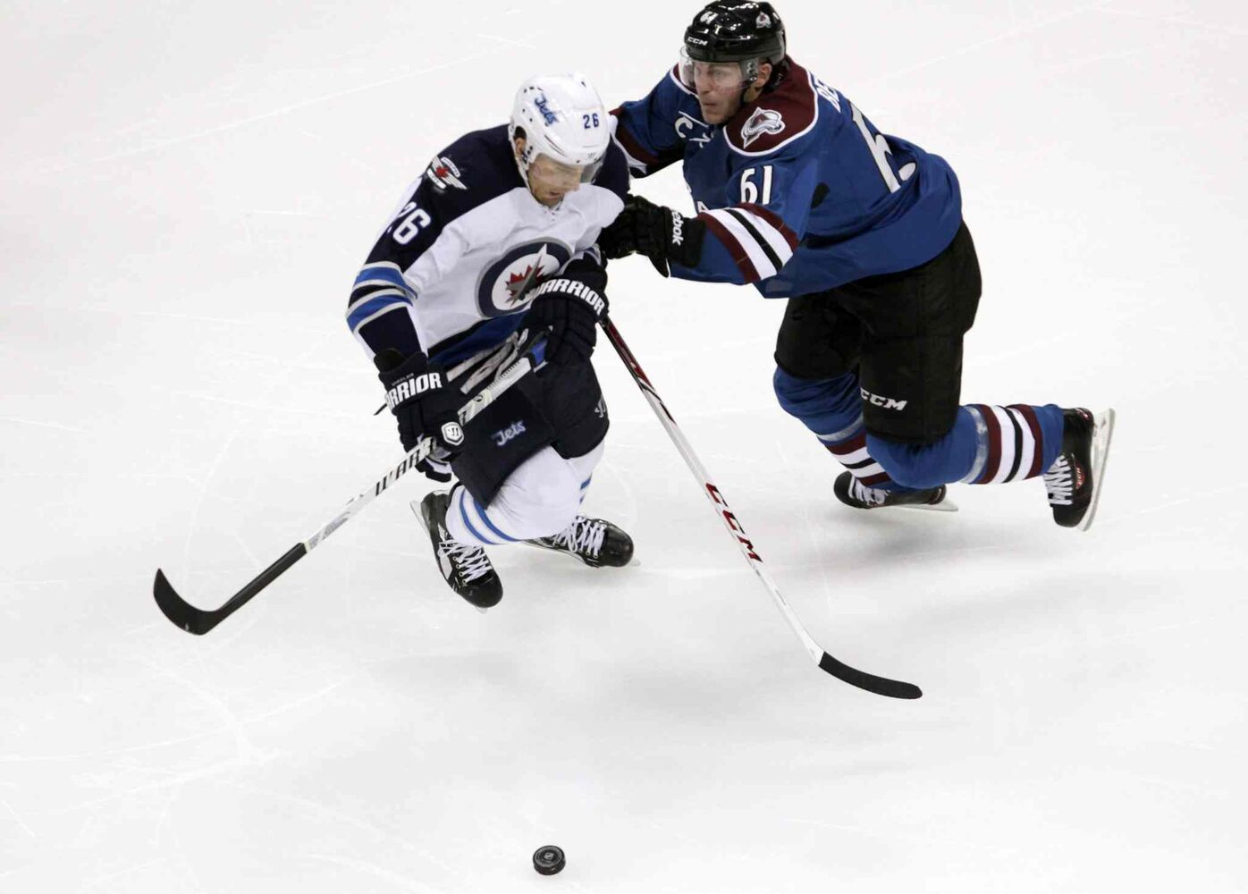 Colorado Avalanche defenceman Andre Benoit (right) pushes Winnipeg Jets winger Blake Wheeler away from the puck during the first period of Sunday's game in Denver, Colo.