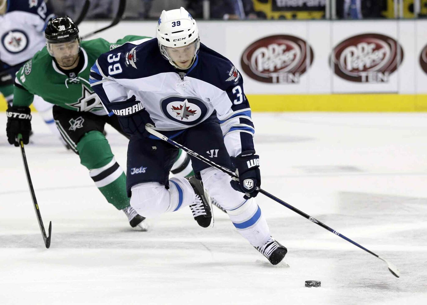 Winnipeg Jets defenceman Tobias Enstrom controls the puck as Dallas Stars forward Vernon Fiddler (gives chase in the first period. (Tony Gutierrez / The Associated Press)