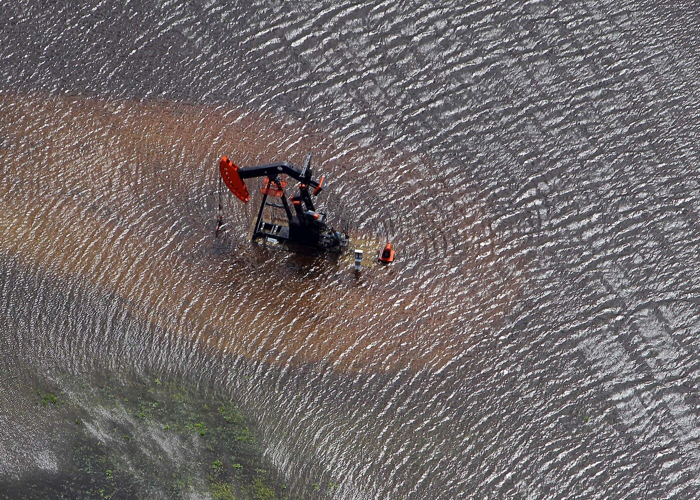 Oil and water mix as floodwaters overrun fields near Cromer, Manitoba on Monday afternoon.