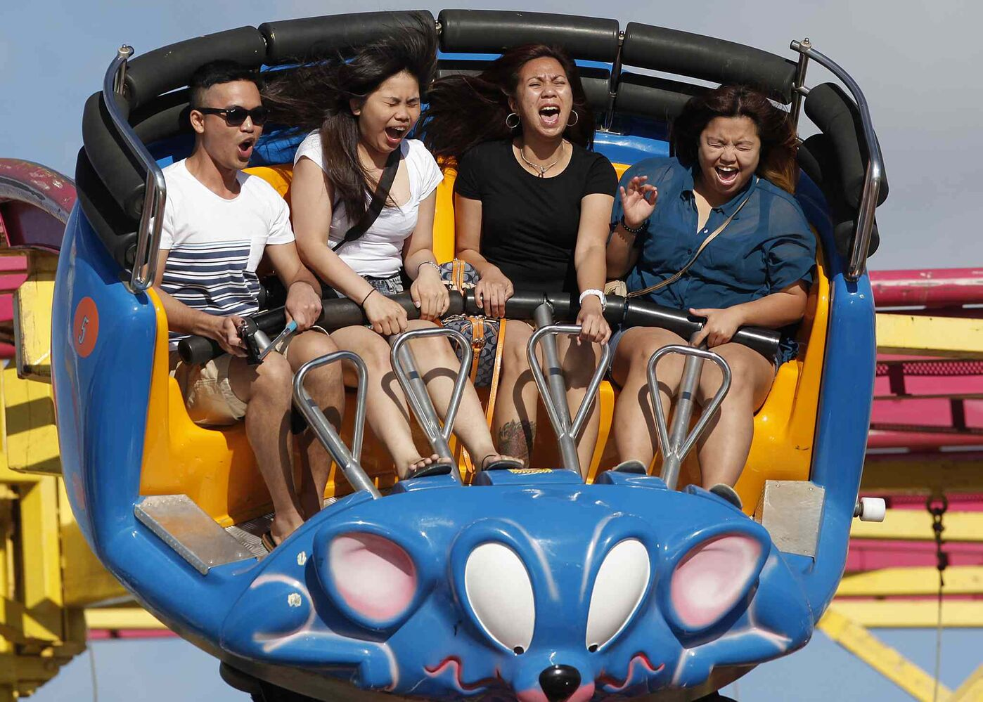 From left, Ace Martin Prieto, Norlyn Brual, Cynthia Berces and Naldine Reyeson take a ride on the Crazy Mouse at The Red River Ex on Tuesday. (John Woods / Winnipeg Free Press)
