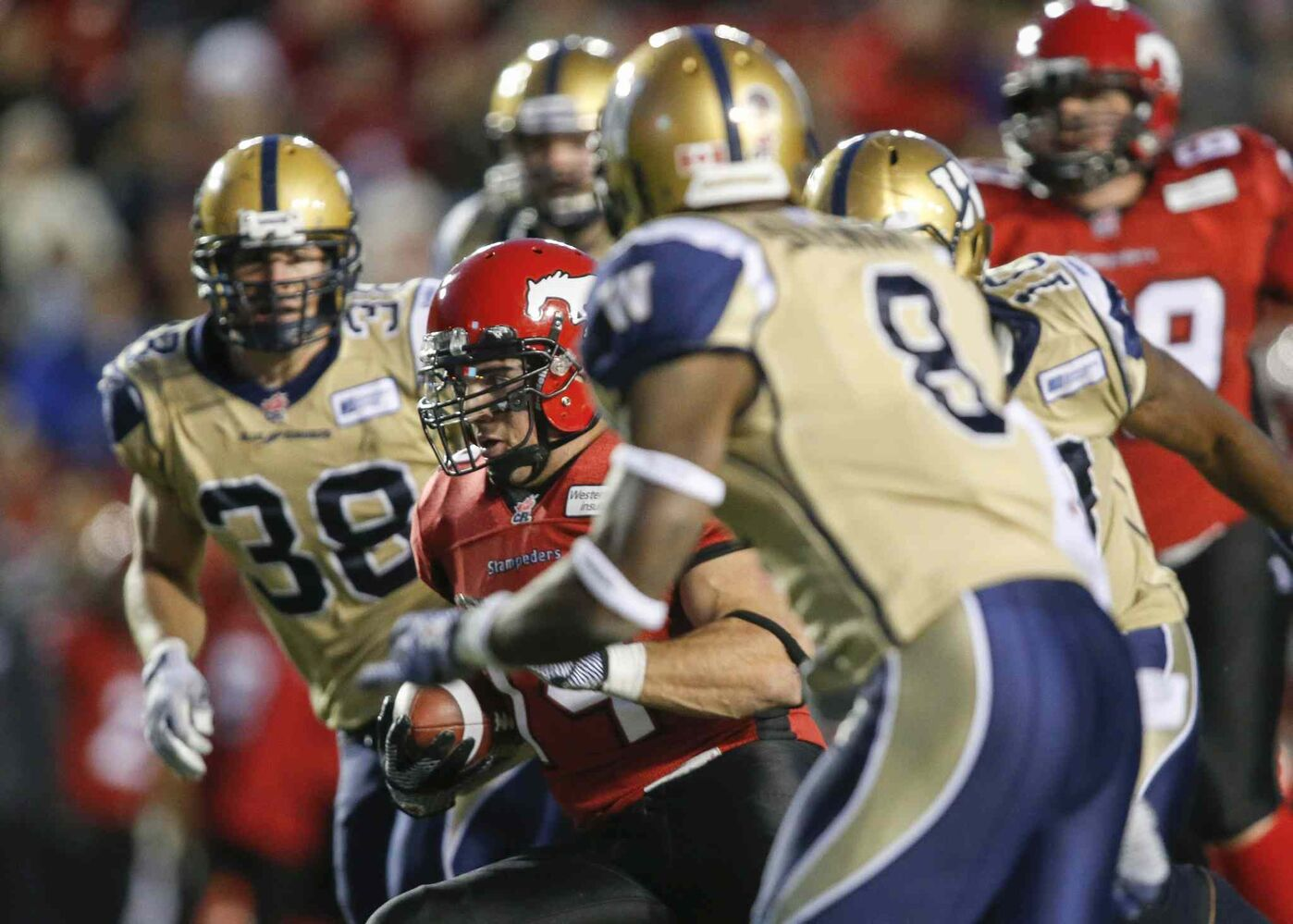 Winnipeg Blue Bombers' Ian Wild (left) and Brandon Stewart (right) close in on Calgary Stampeders' Matt Walter (centre) during the second half. (Jeff McIntosh / The Canadian Press)