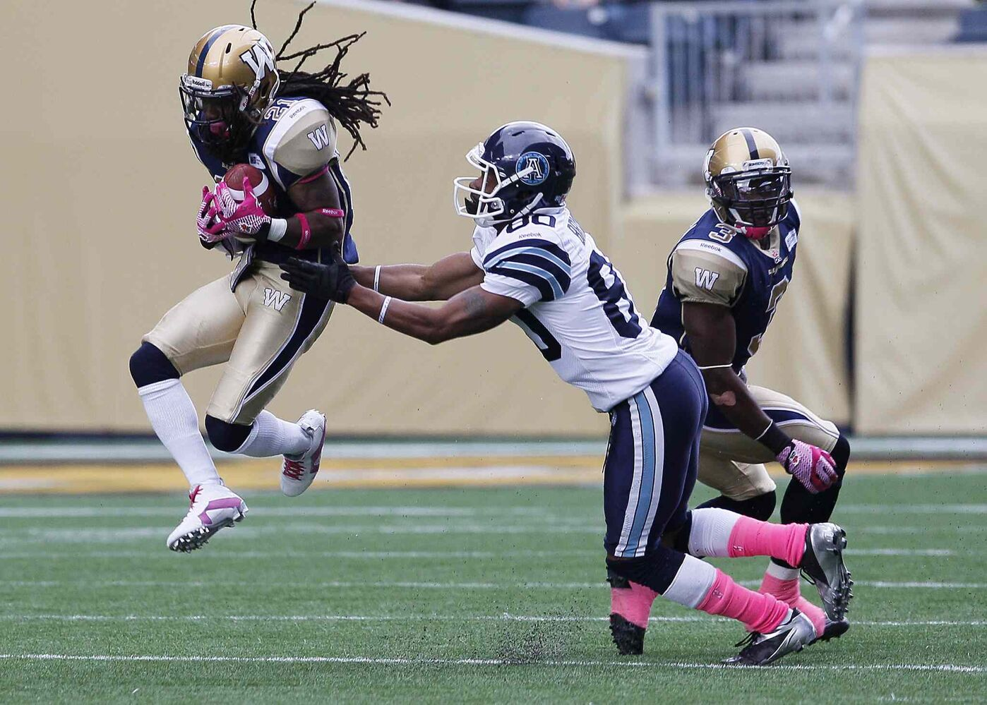 Winnipeg Blue Bombers' Alex Suber (21) snags the pass in front of Toronto Argonauts' Romby Bryant (80).