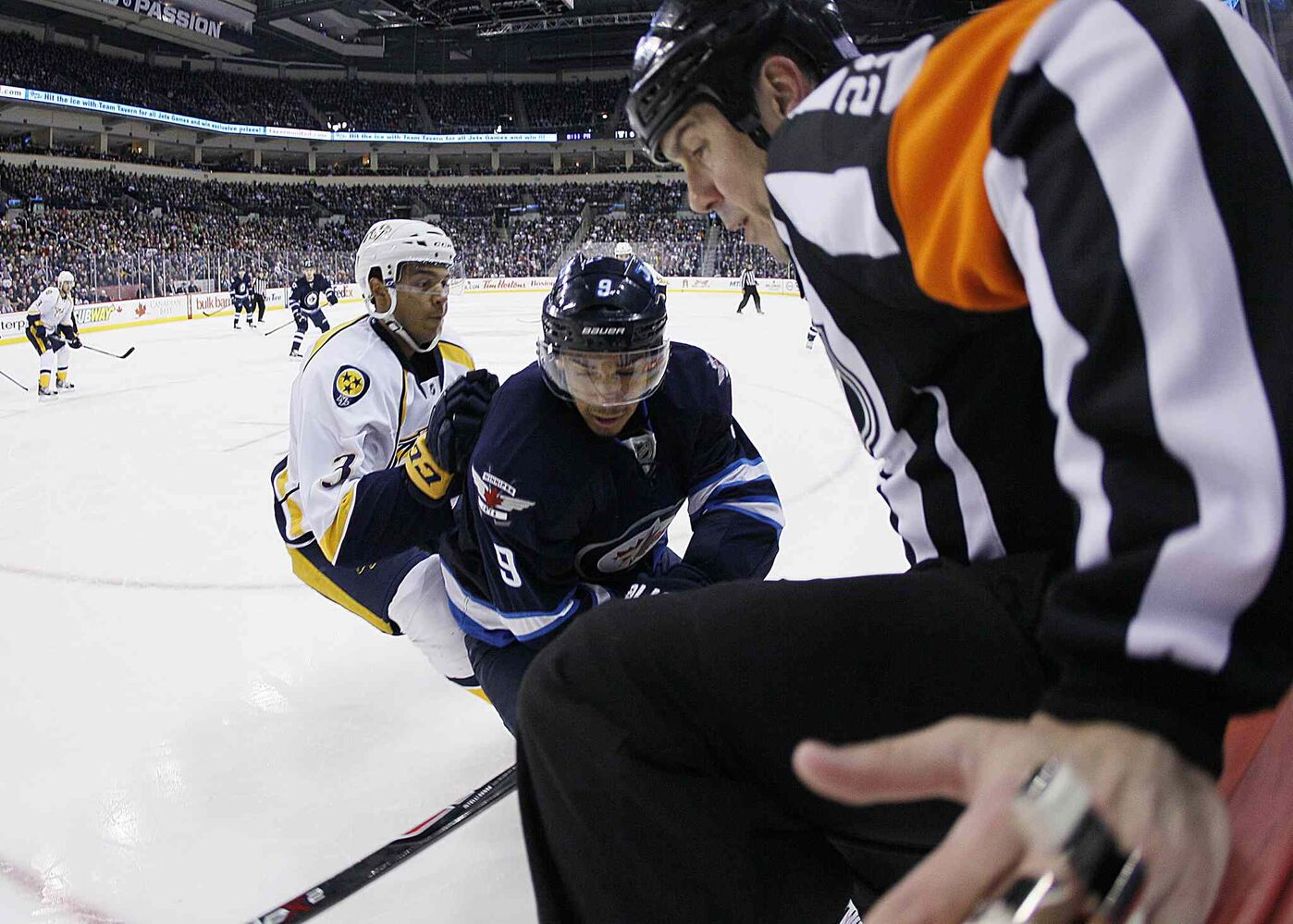 A referee attempts to get out of the way of Nashville Predators' Seth Jones' (3) check on Evander Kane (9) during the second period.
