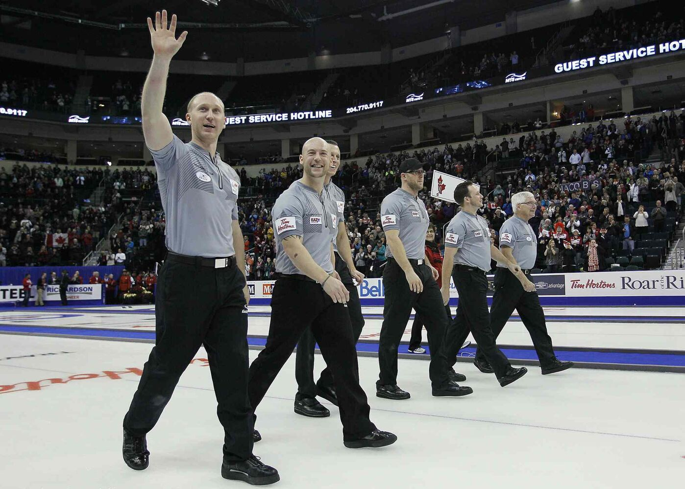 Skip Brad Jacobs (left) and his team acknowledge the crowd as they make their way down the ice after winning the final. (John Woods / The Canadian Press)
