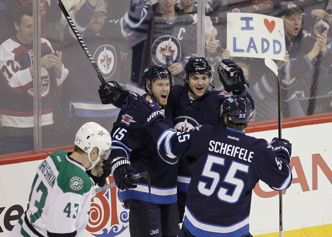 Matt Halischuk (centre left), Michael Frolik (centre right) and Mark Scheifele (right) celebrate Halischuk's first-period goal as Dallas Stars forward Valeri Nichushkin skates. (JOHN WOODS / THE CANADIAN PRESS)