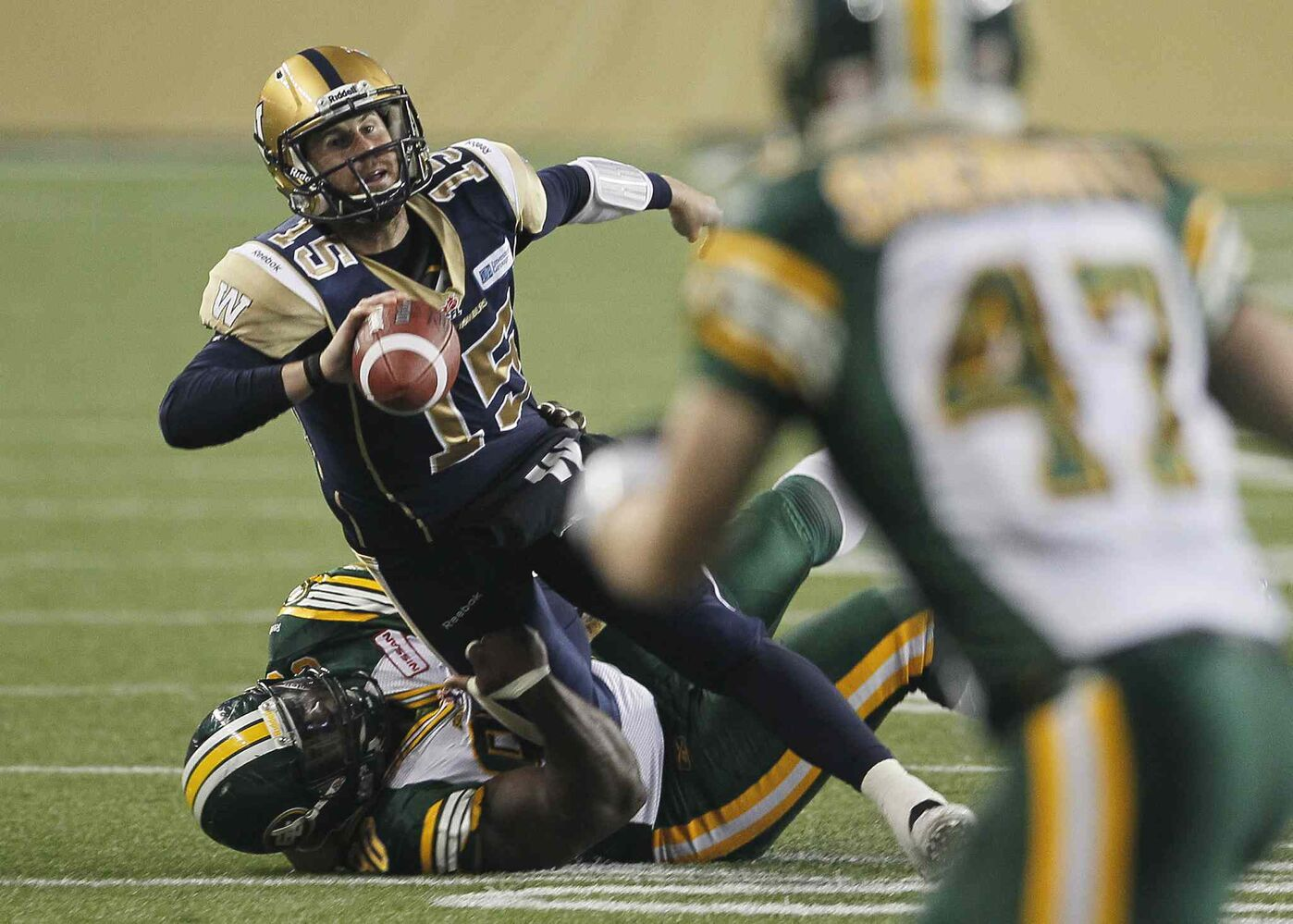 Winnipeg Blue Bombers' quarterback Max Hall (15) is sacked by Edmonton Eskimos' Almondo Sewell (90). (John Woods / The Canadian Press)
