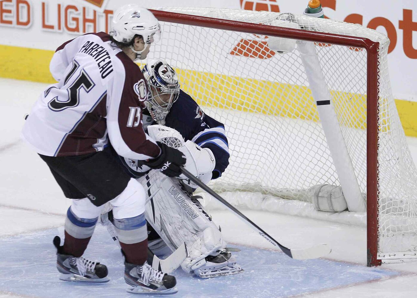 P.A. Parenteau (left) of the Colorado Avalanche scores the game-winning shootout goal shot on Winnipeg Jets goaltender Ondrej Pavelec.